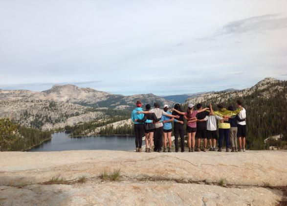 Students stand with arms around each other by the lake