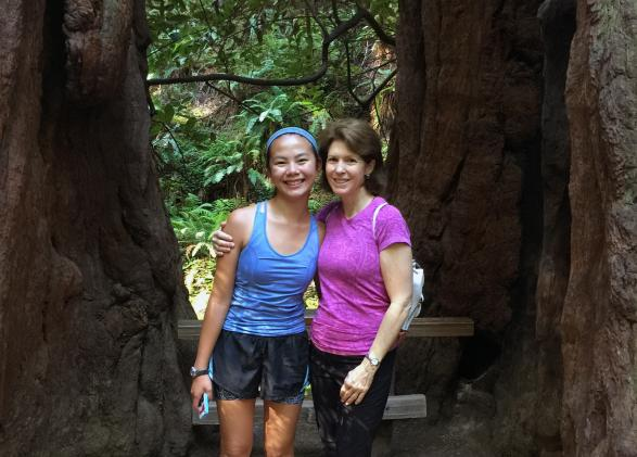 board member Catherine Scott hiking with daughter in the sunny woods