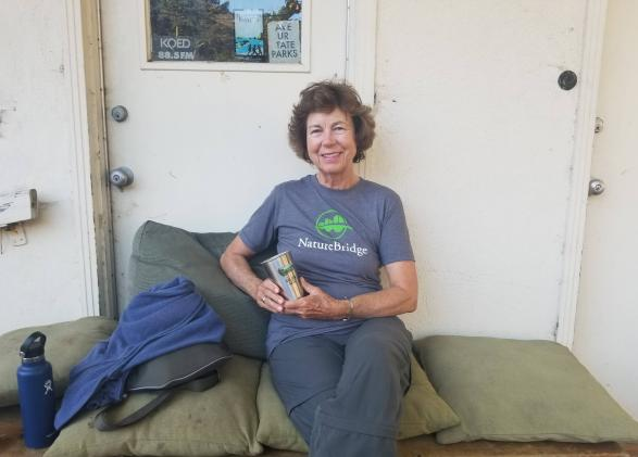 NatureBridge educator Ingrid Apter sitting against a white wall with a cup in hand sitting on green cushions