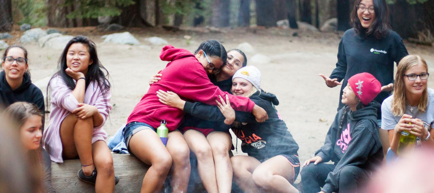 Students hug around a campfire in Yosemite