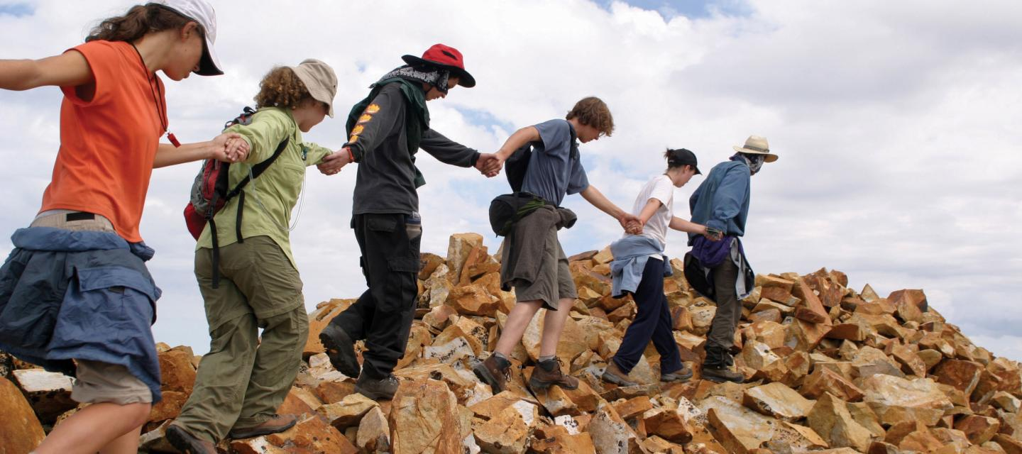 Students join hands to walk across rocks.