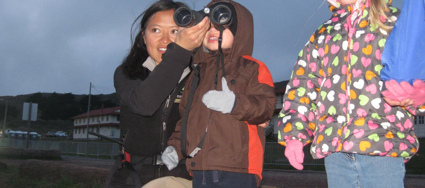 Learning how to use binoculars on a family night hike