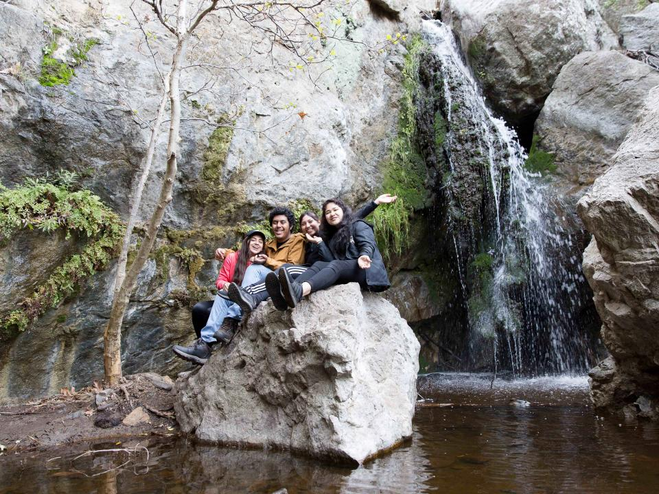 students on rock next to waterfall