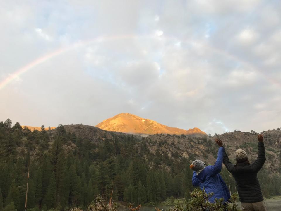 rainbow in yosemite with two scholars holding up their arms
