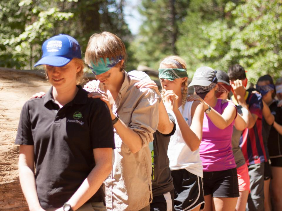 Yosemite educator leading students on walk. Students have bandanas covering their eyes.