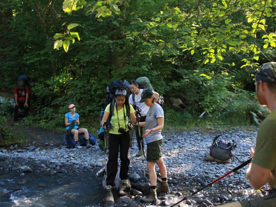 Olympic National Park Ranger helps students cross stream.