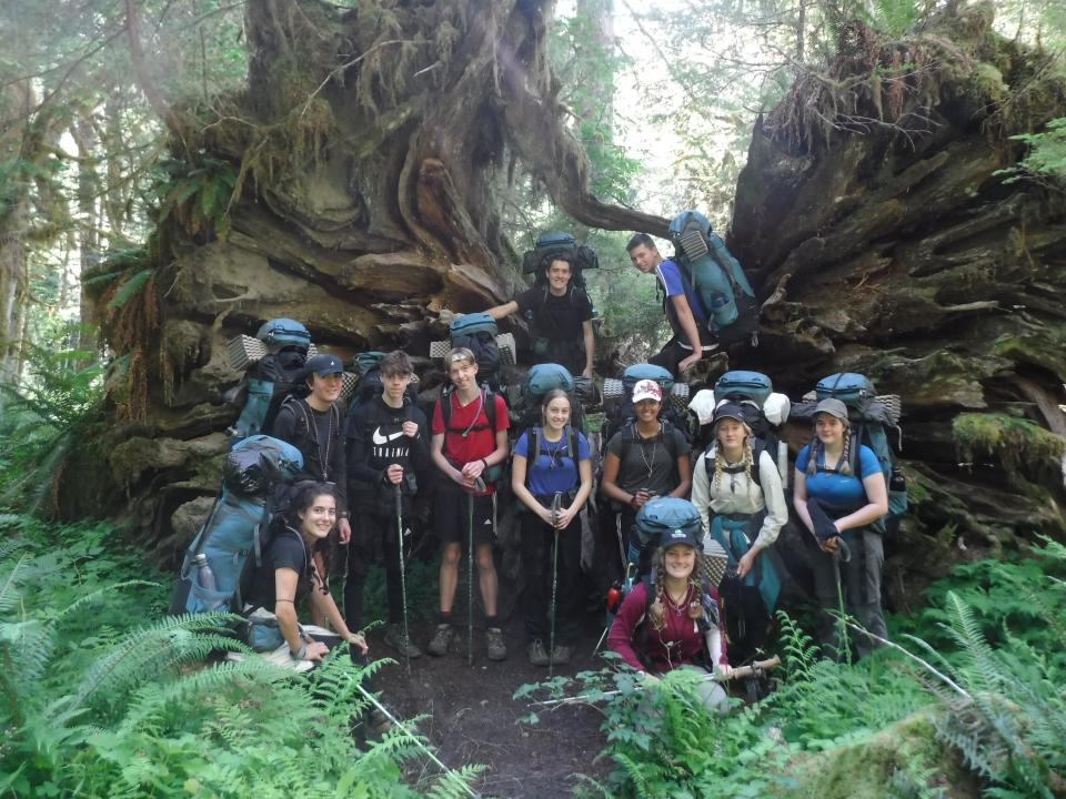 Olympic Alcoa Scholars group photo in front of a massive tree root