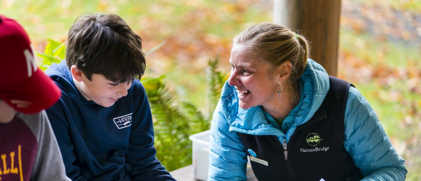A NatureBridge educator laughs with a student in Olympic National Park